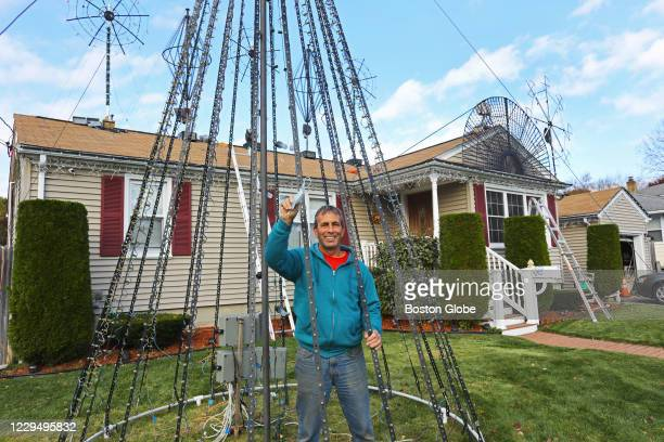 Independent candidate Frank J. Picozzi waves to a neighbor who congratulated him while setting up a computerized Christmas light show outside his...