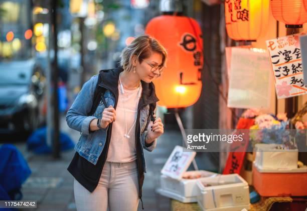 夕暮れ時の新宿で独立した白人観光客ショッピング - 観光 ストックフォトと画像