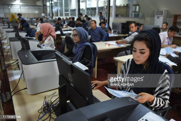 Independent Election Commission workers sit at a computer terminal while election information from all over the country is gathered at the Data...