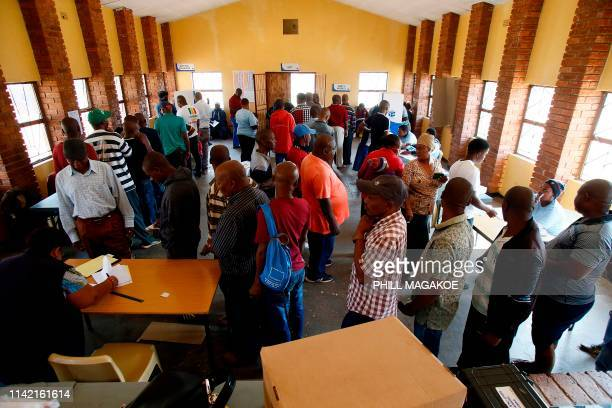 Independent Electoral Commission officials assist residents of Marikana to cast their votes at Thusanang Community Hall during South Africa's...