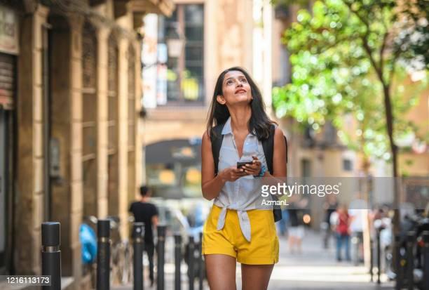 ガイダンスのためのスマートフォンを持つ独立した女性観光客 - 接近する 女性 ストックフォトと画像