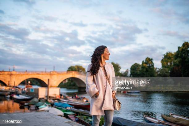 independent female traveler standing on richmond embankment - richmond upon thames stock pictures, royalty-free photos & images