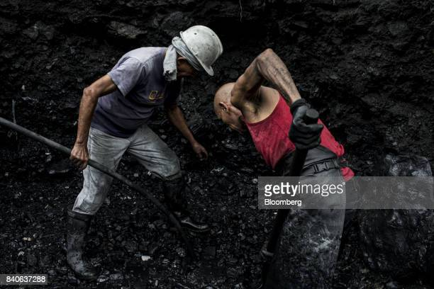 Independent miners know as guaqueros sift through mud and rocks searching for emerald stones that have been washed downstream from the mines in Muzo...
