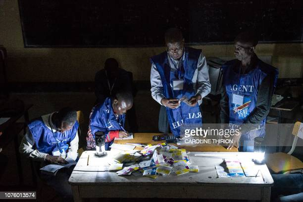 Independent National Electoral Commission agents count votes during an electricity cut while watched by observers at Kiwele college in Lubumbashi on...