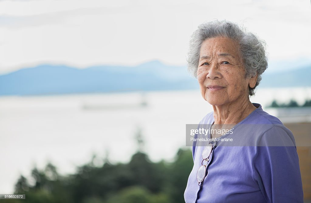 Independent Senior Asian Woman Enjoying View from Apartment, Vancouver, Canada : Stock Photo