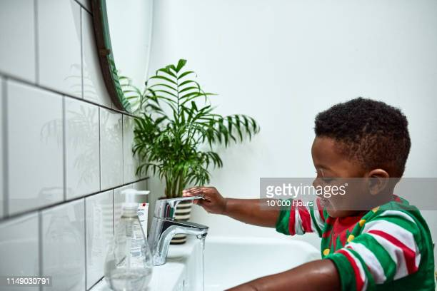 independent toddler washing hands alone at sink - turning on or off stock pictures, royalty-free photos & images
