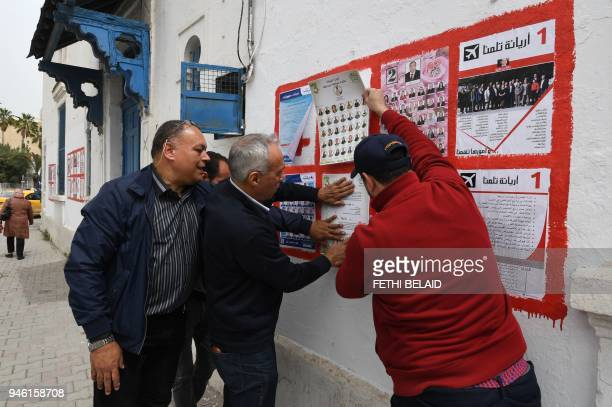 Independent Tunisian candidates hang campaign posters for the upcoming municipal elections in the Tunis suburb of Ariana on April 14 2018 Tunisia...