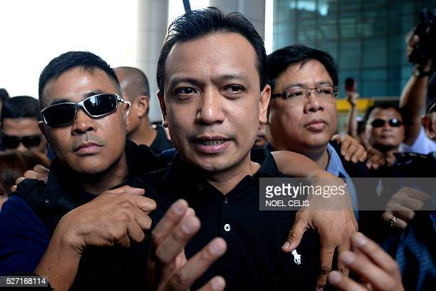 Independent vice presidential candidate Antonio Trillanes is escorted by his aide as he leaves the premises of the Bank of the Philippine Island in...