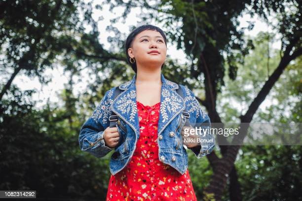 young woman standing in forest holding on to backpack straps while looking away with trees in the background - plan moyen angle de prise de vue photos et images de collection