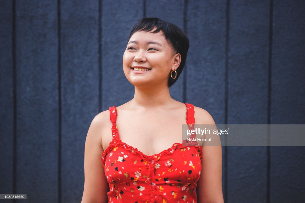 Young woman standing in front of blue wall while smiling and looking away : Stock Photo
