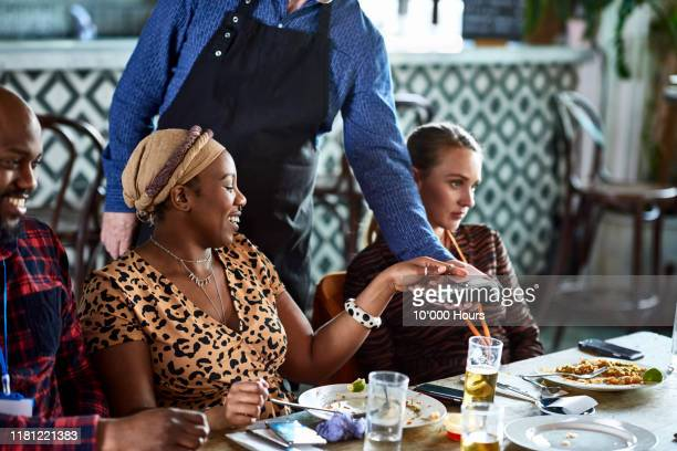 independent woman paying waiter on contactless card machine - paying stock pictures, royalty-free photos & images