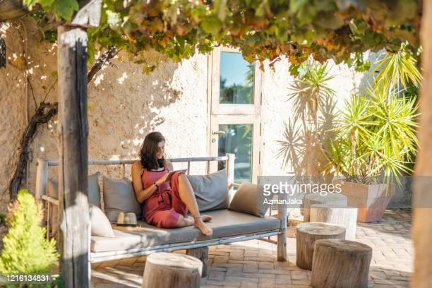 デジタルタブレットで屋外でリラックス独立した女性 - 中庭 ストックフォトと画像