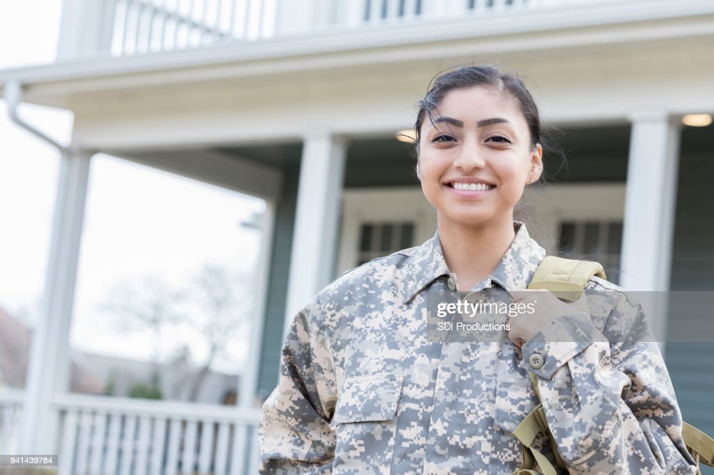 Independent young female soldier departs for overseas deployment : Stock Photo