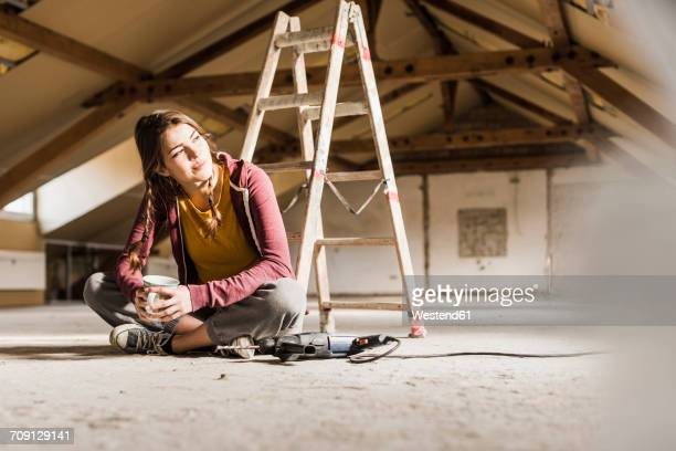 Independent young woman renovating her new home, sittiing on floor with cup of coffee