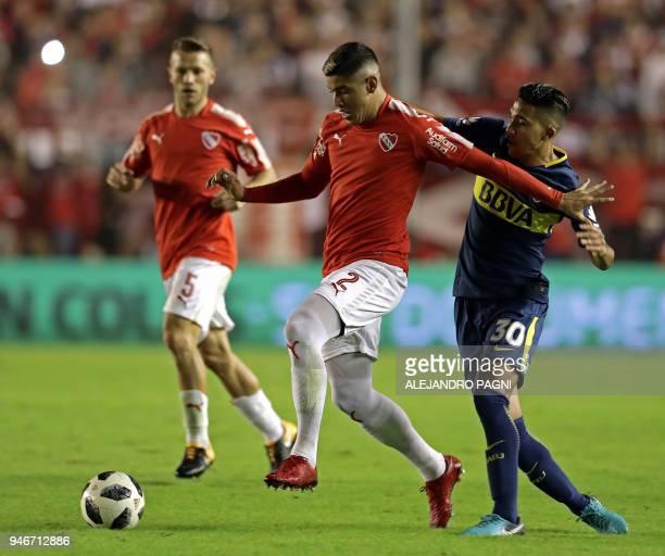 Independiente's defender Alan Franco is challenged by Boca Juniors' midfielder Emanuel Reynoso during their Argentina First Division Superliga...