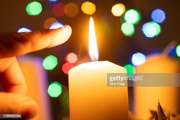 index finger of a person almost touching the flame of the candle. - self harm stock pictures, royalty-free photos & images