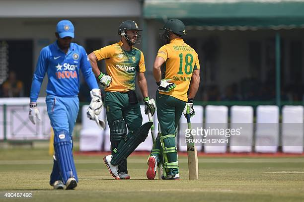 India A wicketkeeper Sanju Sampson walks past South African captain Faf du Plessis and cricketer AB deVilliers during the practice match between the...