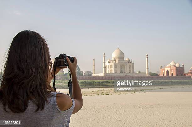 India, Agra, Young woman taking photo of Taj Mahal