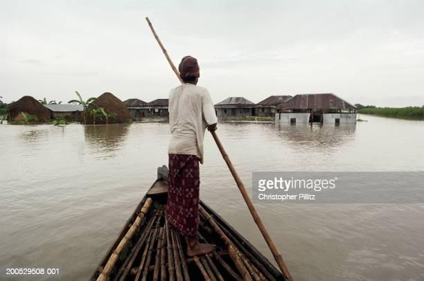 india, bangladesh, boy boating through flooded village, rear view - bangladeshi man stock photos and pictures