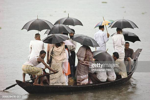 India, Bangladesh, people crowded onto boat holding umbrellas in flood.