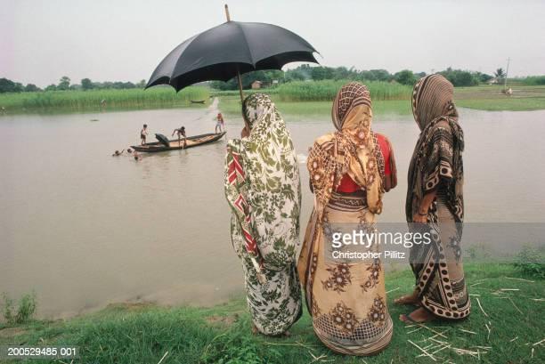 India, Bangladesh, three women on riverbank facing people on boat