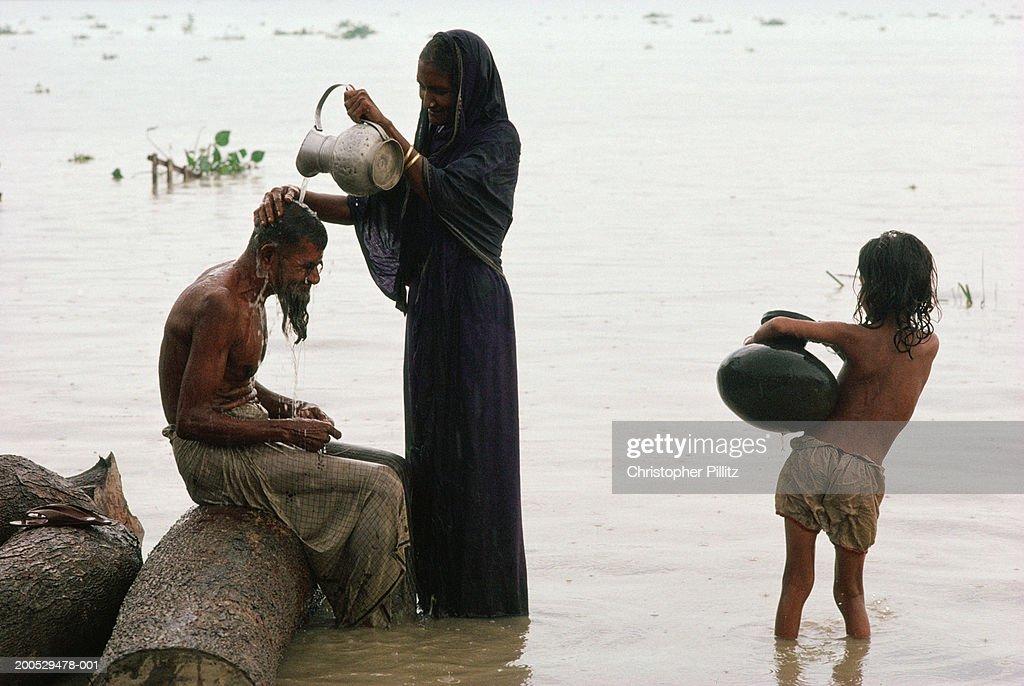India, Bangladesh, woman standing in river washing man's hair : Stock Photo