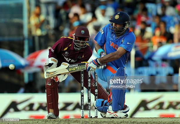 India batsman Yuvraj Singh hits a boundary as West Indies wicketkeeper Devon Thomas looks during the Cricket World Cup match between India and West...