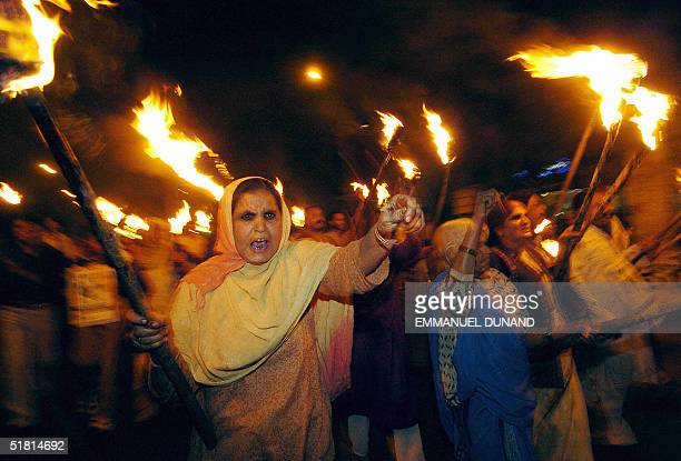 Bhopal gas leak victims march hold torches and shout slogans against Union Carbide pesticide plant at the start of an evening of commemoration to...