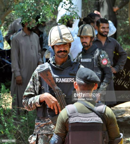 India Border Security Force soldier back to camera and Pakistani Ranger face to camera stand during the ancient shrine of Dalip Singh Baba Chamliyal...