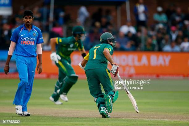 India bowler Jasprit Bumrah walks by South African batsmen Aiden Markram and Hashim Amla making their grounds during the fifth One Day International...