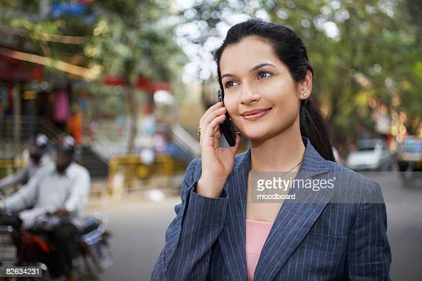 India, business woman using mobile phone on street