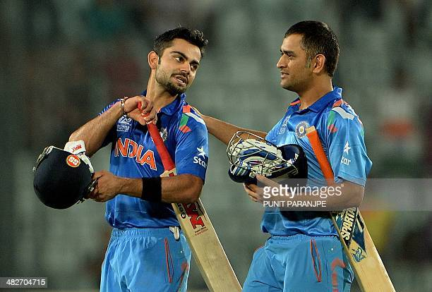 India captain Mahendra Singh Dhoni greets batsman Virat Kohli after India won the ICC World Twenty20 cricket tournament second semifinal match...