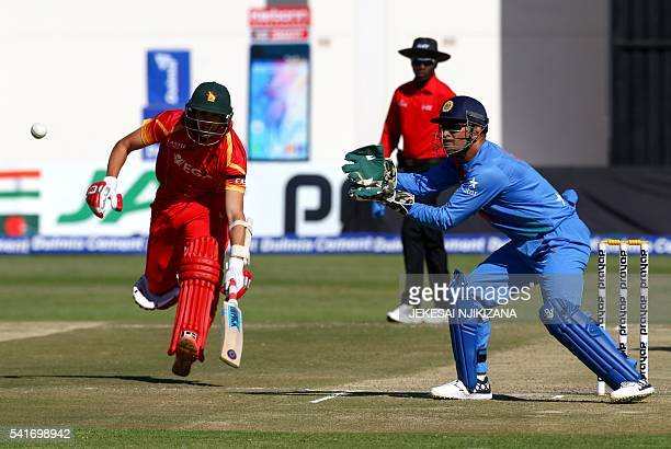 India captain MSDhoni fields as Zimbabwe captain Graeme Cremer runs between the wickets during the second Twenty20 cricket match in the threematch...