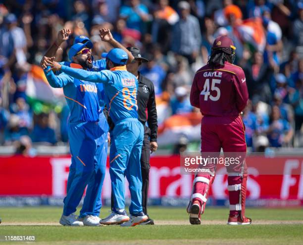 India captain Virat Kohli celebrates with Kedar Jadhav after India take the wicket of Chris Gayle of the West Indies during the Group Stage match of...