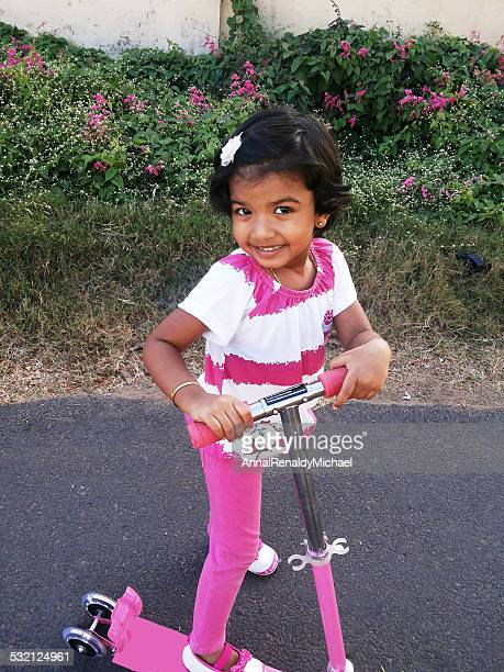 India, Chennai, Portrait of girl (2-3) on pink push scooter, smiling at camera