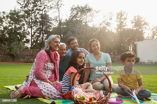 India, Children (4-5, 6-7) with parents and grandparents having picnic on backyard