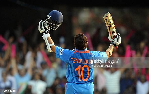 India cricketer Sachin Tendulkar raises his bat to celebrate his century during Cricket World Cup match between England and India at The M...