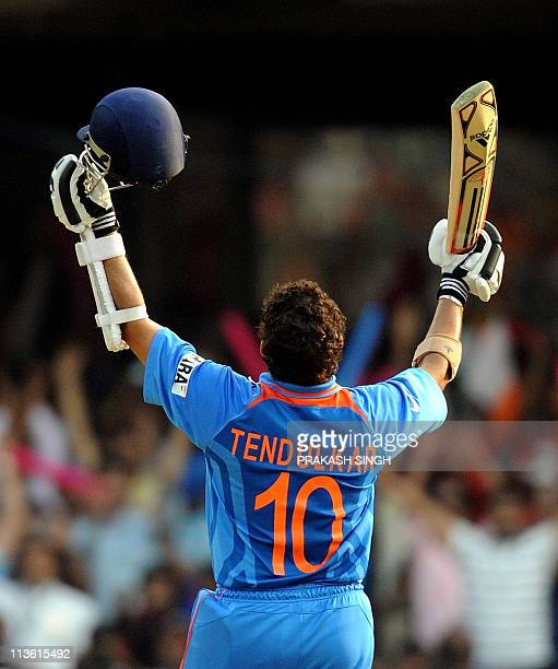 India cricketer Sachin Tendulkar raises his bat to celebrate scoring a century during the Cricket World Cup match between England and India at The M...