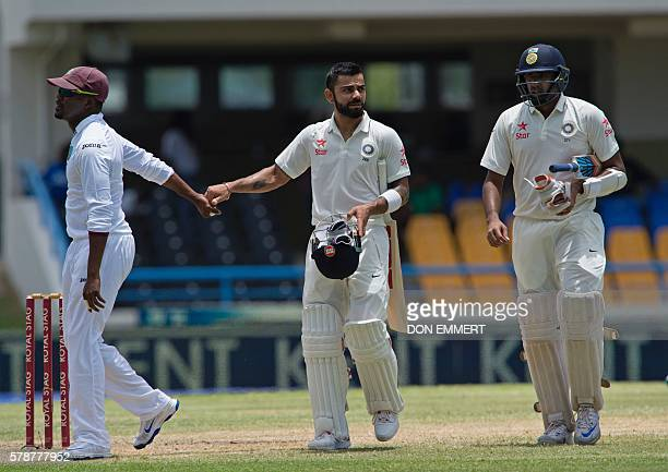 India cricketer Virat Kohli is congratulated by West Indies players after batting 200 runs during day two of the cricket test match between West...