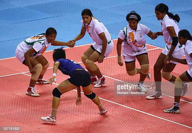 India defend against the raid of Atchara Puangngern of Thailand in the Women's Kabaddi final at Nansha Gymnasium during day fourteen of the 16th...