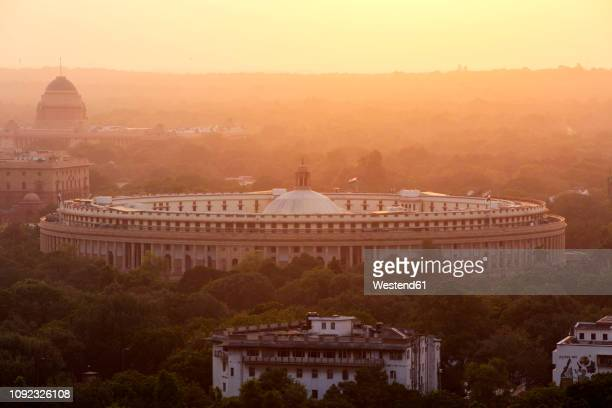 india, delhi, new delhi, parliament building at sunset, pollution, smog - india politics stock pictures, royalty-free photos & images