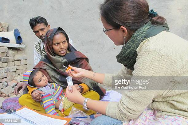POOTHA India Doctor Pooja Kapoor examines an 18month old baby girl suffering from fever and partial paralysis for signs of polio as her parents look...