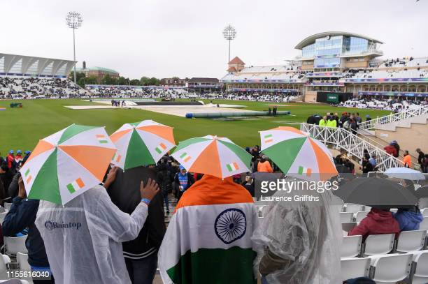 India fans look on as the rain falls during the Group Stage match of the ICC Cricket World Cup 2019 between India and New Zealand at Trent Bridge on...