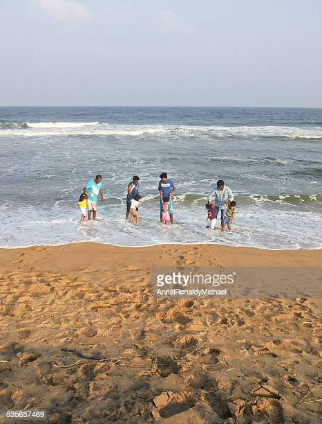 India, Fathers and children (2-7) playing on beach