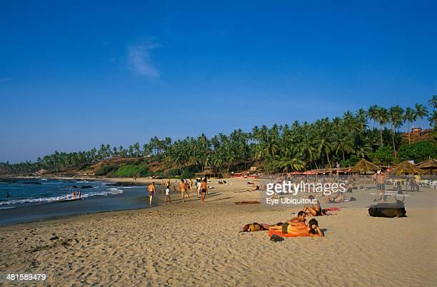 India Goa Little Vagator Beach View along beach people sunbathing and beach bar on right