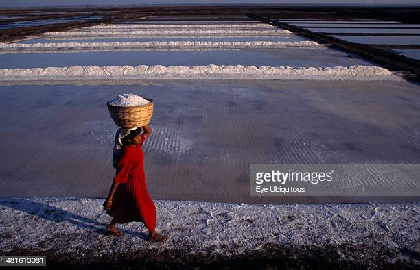 India Gujarat Diu Woman wearing red carries salt in basket on her head across white salt pan