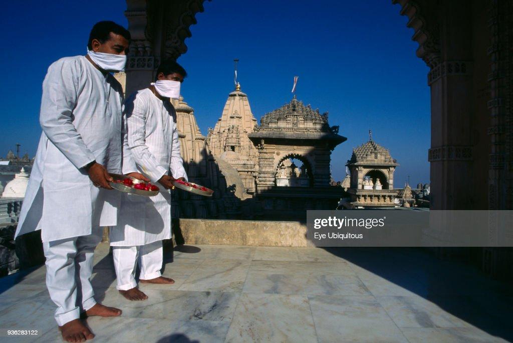 India, Gujarat, Palitana, Jain pilgrims with offerings of flowers at Shatrunjaya or Place of Victory hilltop temple complex and historic Jain pilgimage site. : News Photo
