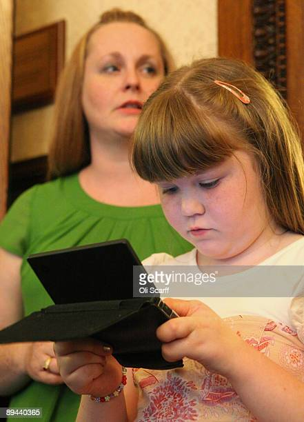 India Harrison 9 plays a computer game as she waits with her mother Johann Harrison at the Law Society following a ruling that Corby Council have...