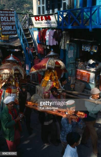 India Himachal Pradesh Kullu Men carrying decorated figures of temple gods through street during Dussehra Festival