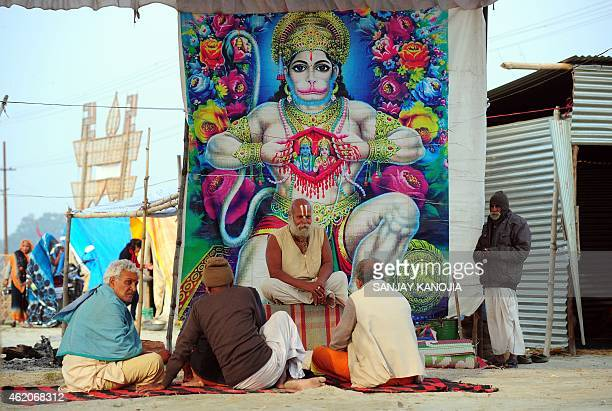 India Hindu devotees sit alongside a poster bearing the image of the Hindu god Hanuman after bathing at Sangam confluence of rivers Ganges Yamuna and...